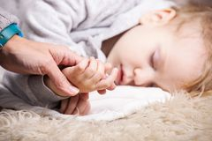 Mother holding son's hand while he is sleeping Stock Images