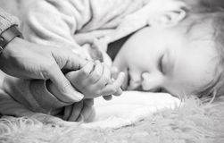 Mother holding son's hand while he is sleeping Royalty Free Stock Photos