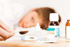 Mother holding spoon with meds for sick kid boy. Mother holding spoon with liquid medicinal product for sick kid boy Stock Image