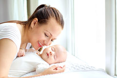 Mother holding sweet baby girl  near the window. Stock Image