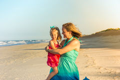 Mother holding toddler daughter on beach Stock Photography