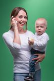 Mother holding toddler son with toy phone Royalty Free Stock Image
