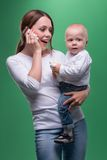 Mother holding toddler son with toy phone Stock Image