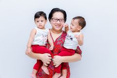 Mother holding two baby Boys. Great happiness, happy young mom with two twins baby. Portrait of young mother holding her little tw. Ins. Beautiful happy mother stock photo
