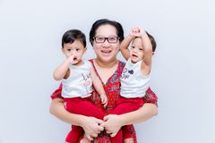 Mother holding two baby Boys. Great happiness, happy young mom with two twins baby. Portrait of young mother holding her little tw. Ins. Beautiful happy mother royalty free stock photography