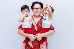 Mother holding two baby Boys. Great happiness, happy young mom with two twins baby. Portrait of young mother holding her little tw. Ins. Beautiful happy mother stock photos