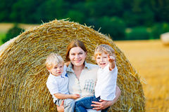Mother holding two children on arms on wheat field in summer Stock Images