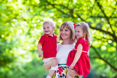 Mother holding two kids walking in summer park Royalty Free Stock Image