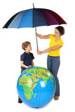 Mother holding umbrella under globe and son. Mother holding umbrella under big inflatable globe and her son, isolated on white royalty free stock photos