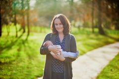 Mother holding 4 weeks old baby girl in her arms. 1 month old child in mommy`s hands outdoors. First walk for a newborn Royalty Free Stock Photo