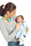 Mother holding yawning baby Stock Images