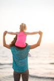 Mother holding young daughter on shoulders at sunset on beach Royalty Free Stock Images