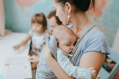Mother holds a baby while father helps his little daughter to make a lessons at the desk in the room with the map on the stock photography