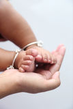 Mother holds baby feet in hands. Royalty Free Stock Images