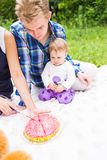 Mother holds cake before little baby daughter stock photography