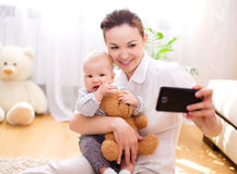 Mother holds child, indoors shoot Royalty Free Stock Images
