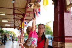 Mother holds daughter in her arms, girl and child beat the bell at the station in Huahin Thailand. royalty free stock images