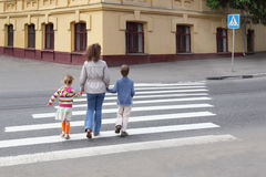 Mother holds hand of children and crossing road. Young mother holds hand of little daughter and son and crossing road, behind, yellow house royalty free stock images