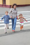 Mother holds hand of children and crossing road. Young mother holds hand of little daughter and son and crossing road, yellow house, focus on boy Stock Image