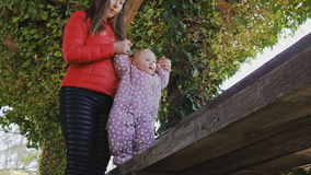 Mother holds hands of baby learning to walk on wooden bench stock video footage