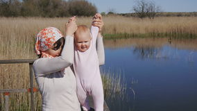 Mother holds hands of baby trying to walk stock video footage
