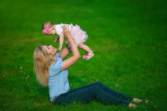 Mother holds on a hands her little baby on a grass Stock Photography