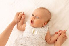 A mother holds the hands of a surprised baby on a white bed