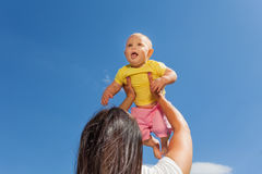 Mother holds her baby up with straight arms Royalty Free Stock Photography