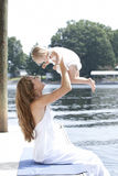 A mother holds her daughter playfully in the air. On a dock by the lake Stock Image