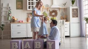The mother holds her daughter`s hands and leads on the cubes, while Dad sits next to him on the floor. stock footage