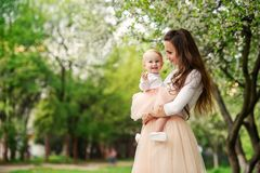 Mother holds her little daughter in her arms among blooming trees. Mom and her little baby weared pink family look dress stock photos