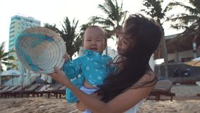 A mother holds her little smiling child in her arms on the beach near palms. stock video footage