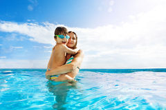 Mother holds her son with goggles, stands in water Stock Image