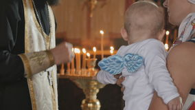 Mother holds a little boy in arms and listens a priest in church stock footage