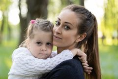 Mother holds a little girl in her arms stock images