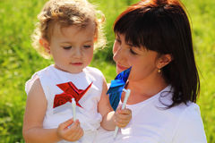 Mother holds the little girl with pinwheels Royalty Free Stock Photography