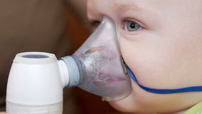 Mother holds the mask on the baby inhaler and breathes the medicine at home. Treats inflammation of the airways via stock footage