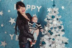 Mother holds newborn baby in sailor sweater at plastic white christmas tree against blue wall background.  Royalty Free Stock Images