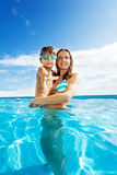 Mother holds son with goggles and smiles in pool. Mother holds her son with goggles and smiles while standing in crystal blue water of swimming pool Stock Images