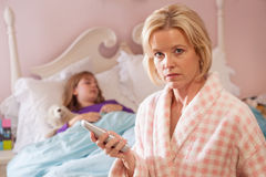 Mother holds telephone while daughter sick in bed. Royalty Free Stock Photography