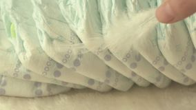 Mother holds a white gentle feather on baby diapers, the concept of comfort and lightness, slow motion. Nappy stock video