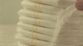 Mother holds a white light feather on baby diapers, the concept of lightness and comfort, close-up, slow mo, background. Mother holds a white light feather on stock video footage