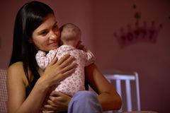 Mother At Home Cuddling Newborn Baby In Nursery Stock Photography