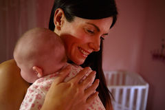 Mother At Home Cuddling Newborn Baby In Nursery Royalty Free Stock Photography