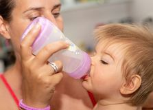 Feeding. Mother. Baby. Eating. Bottle. Cute stock images