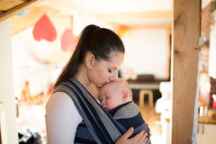 Mother at home with her son in sling, kissing him. Beautiful young mother at home with her baby son sleeping in sling, kissing him on head Royalty Free Stock Photography