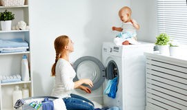 Mother housewife with baby engaged in laundry fold clothes into Stock Photo