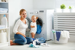 Mother housewife with baby engaged in laundry fold clothes into Stock Image