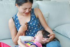 Mother hug her Cute asian child girl age about one year old and nine month drinking from a bottle Stock Photos