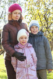 Mother hug son, daughter in autumn forest Stock Photos